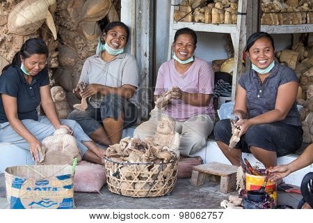 Unidentified women are making wooden souvenirs for tourists.