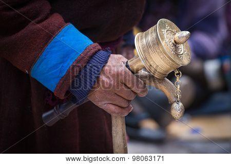 Old Tibetan Man Holding Wooden Walking Stick And Buddhist Prayer Wheel, Ladakh, India