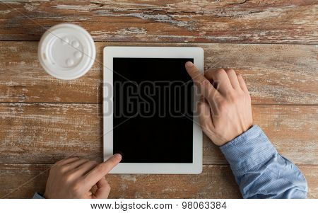 business, education, people and technology concept - close up of male hands with tablet pc computer and coffee paper cup on table