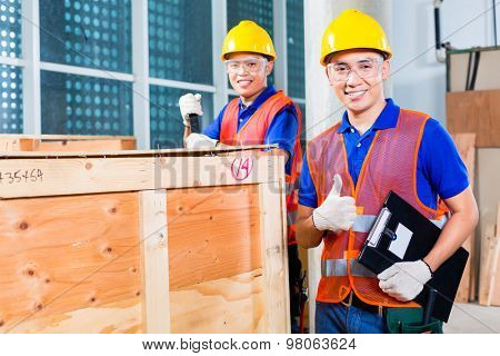 Two Asian Indonesian industrial or construction workers controlling with a checklist a delivery on a tower building site and open a wood box or cargo container with a crowbar