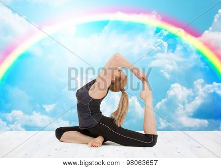 sport, fitness, yoga, people and health concept - happy young woman doing headstand exercise on wooden berth over white clouds and rainbow on blue sky background