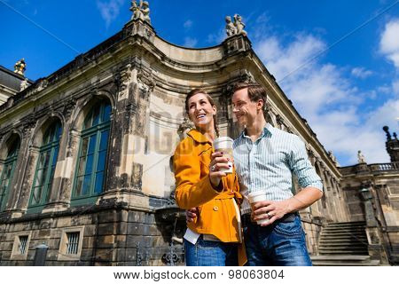 Tourist couple in Dresden at Zwinger with coffee taking walk
