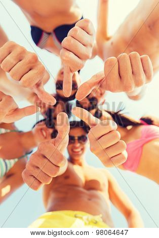 friendship, summer vacation, holidays, gesture and people concept - close up of smiling friends wearing swimwear standing in circle and showing thumbs up over blue sky