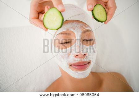 Upward view of woman placing cucumber on patient eye at the health spa