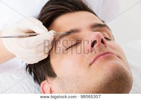Beautician Hands Plucking Man Eyebrows With Tweezers