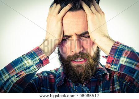 Handsome hipster getting a headache on vignette background