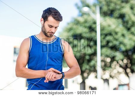 An handsome athlete using his phone on a sunny day