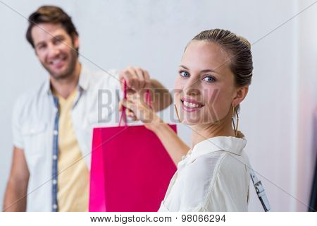 Portrait of smiling cashier giving shopping bag to woman in clothing store