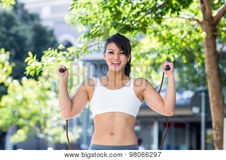 Portrait of smiling athletic woman skipping in the city