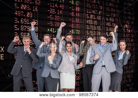 Excited business team cheering at camera against stocks and shares