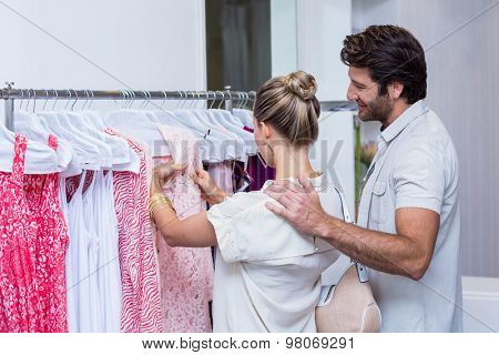 Smiling couple looking at clothes in clothing store