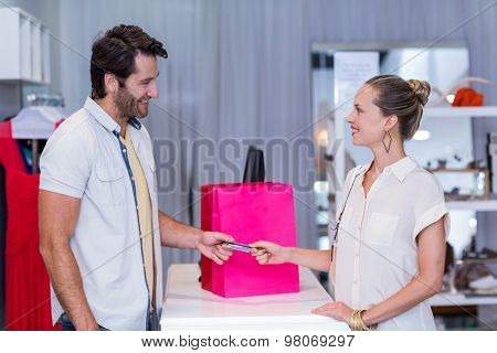 Smiling woman giving credit card to cashier in clothing store