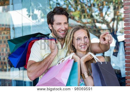 Smiling couple with shopping bags looking and pointing at shopping mall