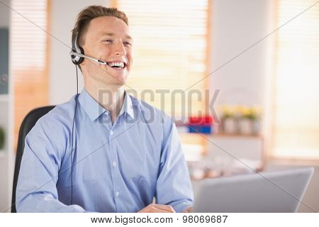 Casual businessman using headset on a call in his office