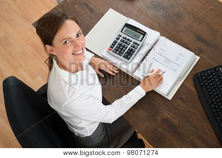 Businesswoman With Invoice And Calculator