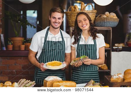 Smiling co-workers showing sandwich and pie at the coffee shop