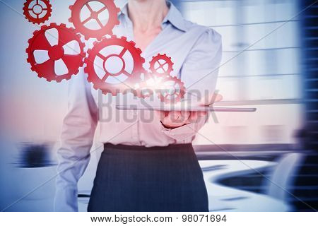 Businesswoman holding digital tablet against laptop on desk with glasses and notepad
