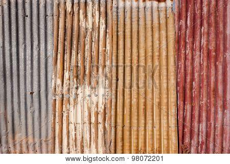 Grunge background of weathered corrugated iron fence panels
