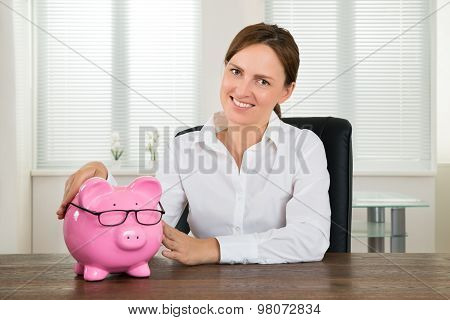 Businesswoman With Piggybank At Desk
