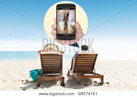 Couple Relaxing On Deck Chairs At Beach Resort
