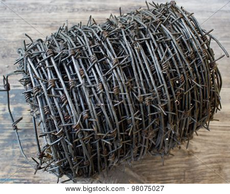 Roll Of Barbed Wire, On A Wooden Background