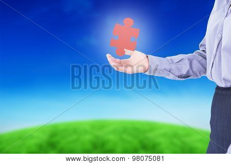 Businesswoman presenting with hand against green hill under blue sky