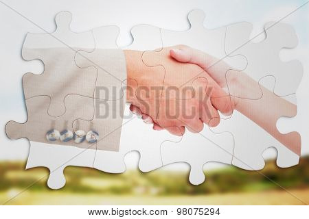 Close up of female and male hand shaking against blue sky over fields