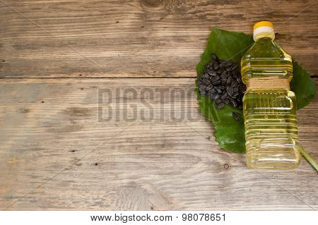 Bottle Of Sunflower Oil And Sunflower Seeds On Wooden Background. Copy Space To Right.
