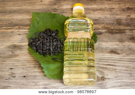 Bottle Of Sunflower Oil And Sunflower Seeds On Wooden Background