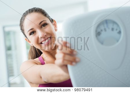 Happy Woman Showing A Scale