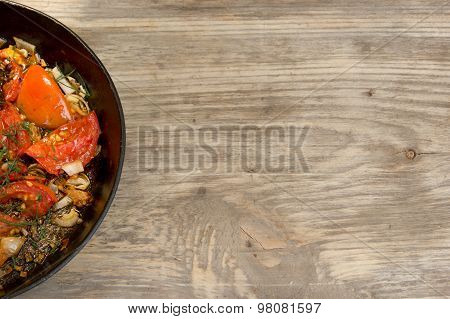 Frying Pan With Scrambled Eggs And Tomatoes On Wooden Rustic Table. Copy Space To Right.