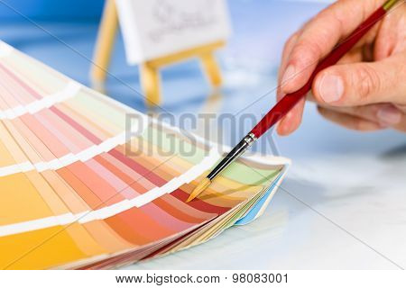 Artist Hand Pointing To Color Samples In Palette With Paintbrush