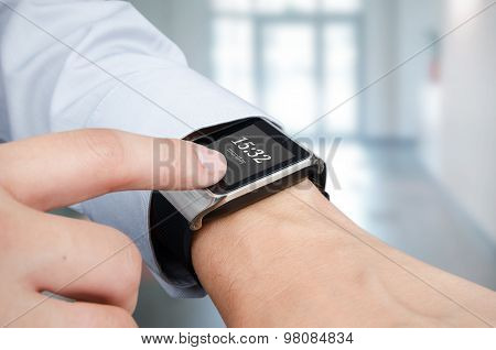 Businessman Checking Time On Smart Watch. Office In Background