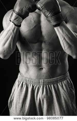The man in boxing gloves. Young Boxer fighter over black background
