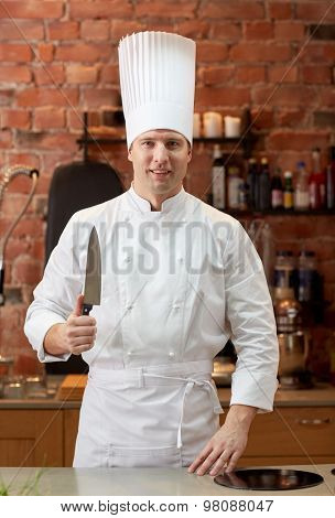 cooking, kitchenware and people concept - happy male chef cook with knife in restaurant kitchen