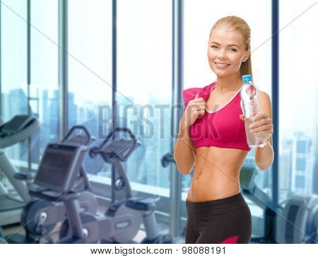 people, sport, fitness and recreation concept - happy woman with bottle of water and towel over gym machines background