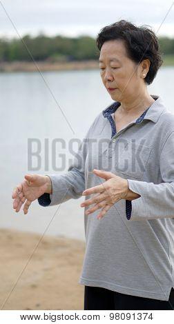 Asian Senior  Practice Taichi, Qi Gong Exercise Next To The Lake