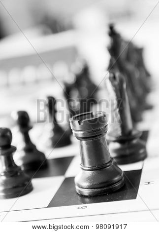 Chess pieces on the board close up. Monochrome image.