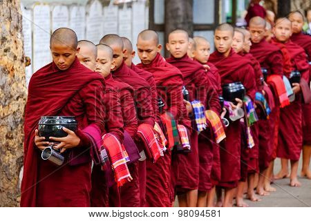 Amarapura, Myanmar - June 28, 2015: Buddhist Monks Queue For Lunch In Front Of Mahagandayon Monaster