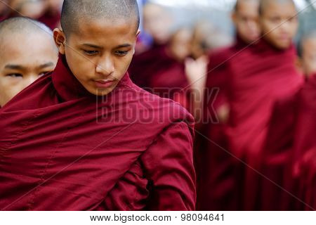 Amarapura, Myanmar - June 28, 2015: Buddhist Monks Queue For Lunch In Front Of Mahagandayon Monaster