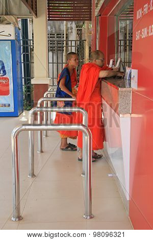 two buddhist monks are buying bulletins