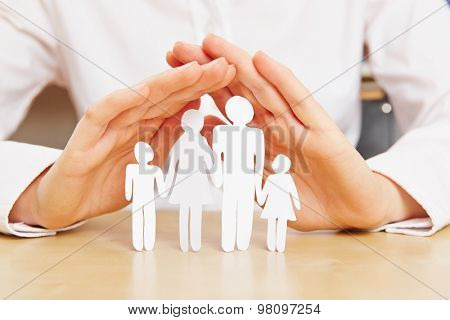 Female hands protecting family with children made of paper