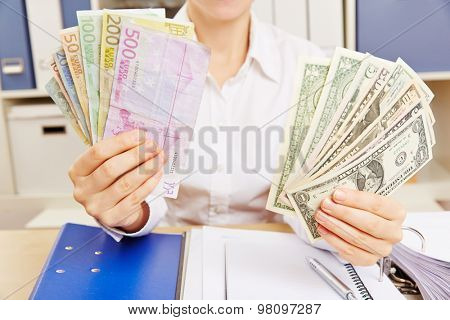 Hands of a business woman holding many Euro and Dollar money bills
