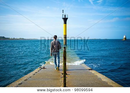 man walking into the sea