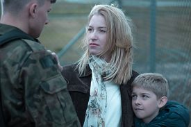 stock photo of say goodbye  - Military soldier saying goodbye to wife and son - JPG