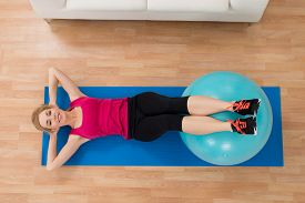 stock photo of pilates  - High Angle View Of Happy Woman Exercising With Pilates Ball On Wooden Floor - JPG