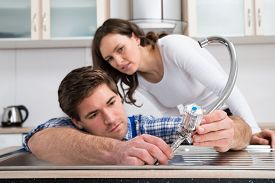 stock photo of tapping  - Young Woman Looking At Plumber Fixing Steel Tap In Kitchen Sink - JPG