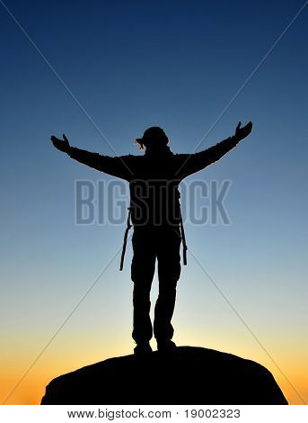 Happy man waiting sunrise on the top of a mountain