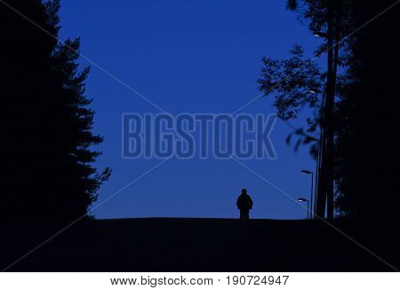Night walk in the street. A person in the first morning light comes down a street on a hill. Lampposts. Silhouettes.