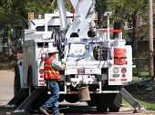 stock photo of lineman  - an electrical lineman working around his utility truck - JPG